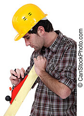 Carpenter using a wood plane
