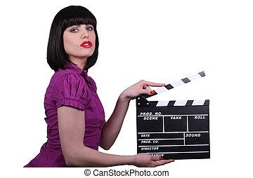 Sexy woman with cinema clap, studio shot