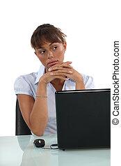 Pensive businesswoman sat at desk