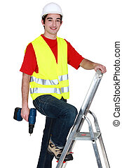 Man standing on ladder with drill