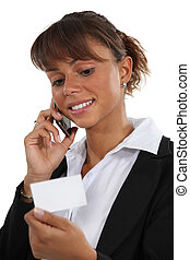Woman on the phone looking at a business card