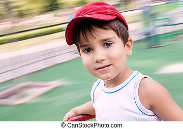 Portrait of a 3-4 years boy playing on the playground with...