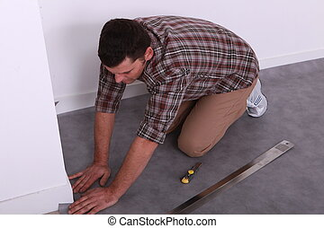 Man on his knees fitting a grey linoleum floor