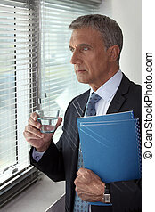 Businessman looking through his office window