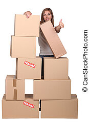 Woman behind a pile of cardboard boxes
