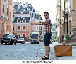 Young man thumbing a ride - Young man with a large suitcase...