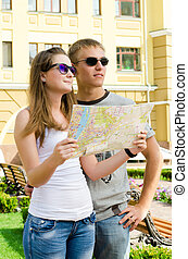 Young couple enjoying a summer vacation standing looking at...