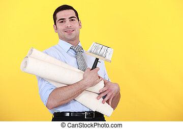 young handsome man carrying rolls of wallpaper against...