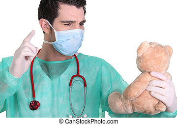 Man dressed as a surgeon quarreling with teddy bear