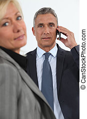 Businessman talking on his mobile phone beside his colleague