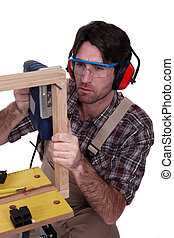 A male carpenter using a jigsaw