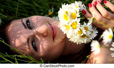 Girl with daisies - Girl lays on the grass with a bouquet of...