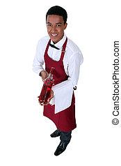 Waiter serving a bottle of rose wine
