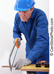 Plumber sawing a pipe