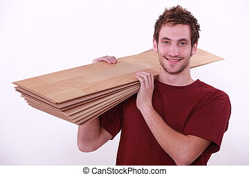 Carpenter carrying floor boards