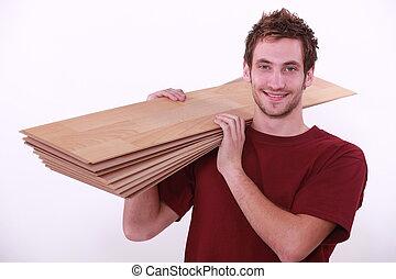 Carpenter carrying floor boards