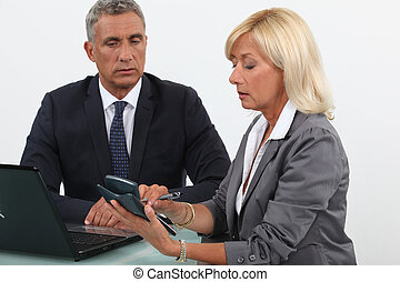Business partners using calculator