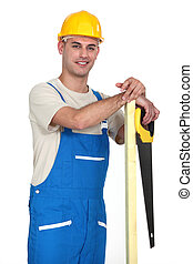 Happy tradesman holding a plank of wood and a saw