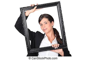 Woman behind black frame