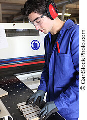 Young factory worker preparing machine
