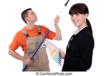 Interior decorator holding colour samples while a man paints