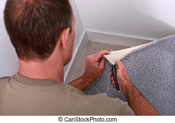 Man cutting carpet to fit a corner of a room