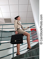 Businesswoman with briefcase climbing stairs