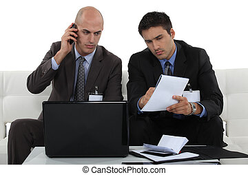 Two businessmen working together on project