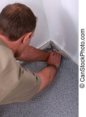 Carpet fitter pushing the edges into a corner