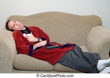 Man With The Flu - A young man laying on a sofa in his...