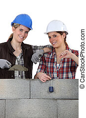 two craftswomen building a wall