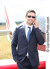 Wealthy businessman in front of an airplane