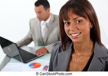Smiling businesswoman standing in front of a colleague and...