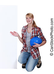 craftswoman posing next to a blank poster