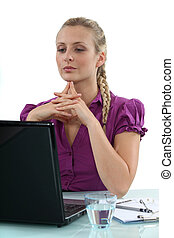 Woman thinking at her laptop