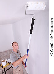Decorator using roller to paint ceiling