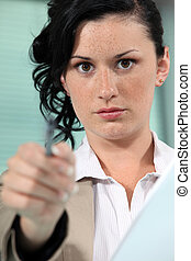 Close-up shot of a woman pointing her pen