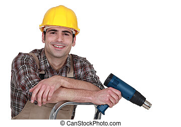 smiling carpenter on ladder with electric drill