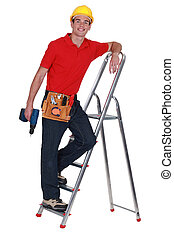 Young tradesman standing on a stepladder and holding a screw...