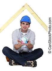 Carpenter sat cross-legged holding house made from bank notes