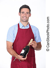 wine steward holding a bottle of champagne