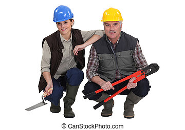 Two kneeled construction workers.