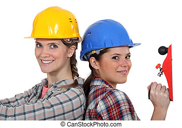 Women in hard hats with a carpenter's plane