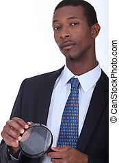 African American man in suit holding a loupe
