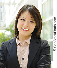Young Executive - Young Asian executive standing outside...