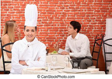 female chef posing in restaurant with couple dining in...