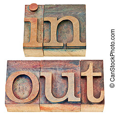 in and out word in wood type - in and out - isolated words...