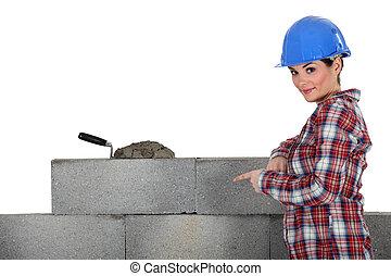 female mason pointing at a wall