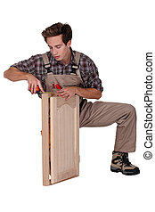 Woodworker crouching on white background