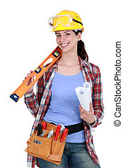 Female construction worker holding tools and a rolled-up...